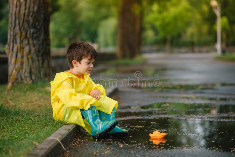 Child playing with toy boat in puddle. Kid play outdoor by rain. Fall rainy weather outdoors activity for young children. Kid royalty free stock photos