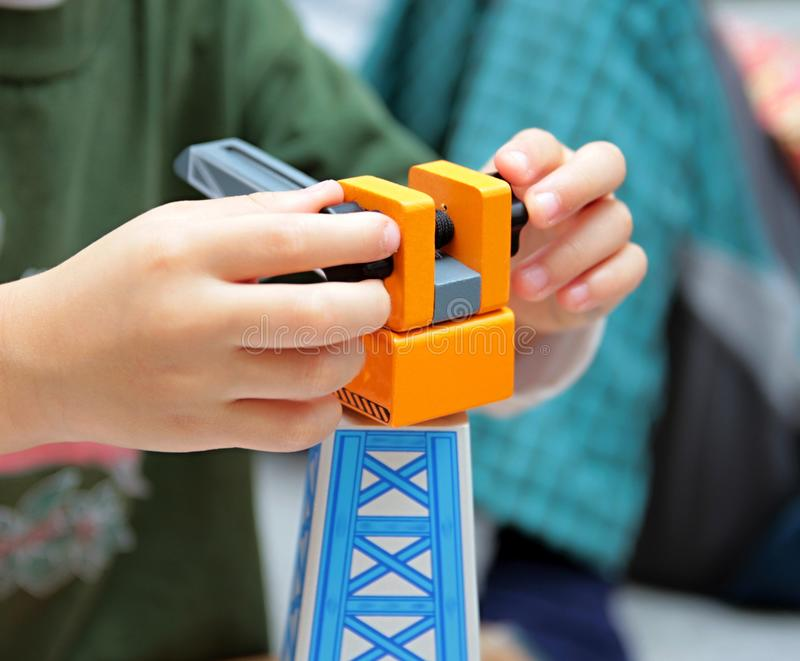 Child playing with toy crane stock image