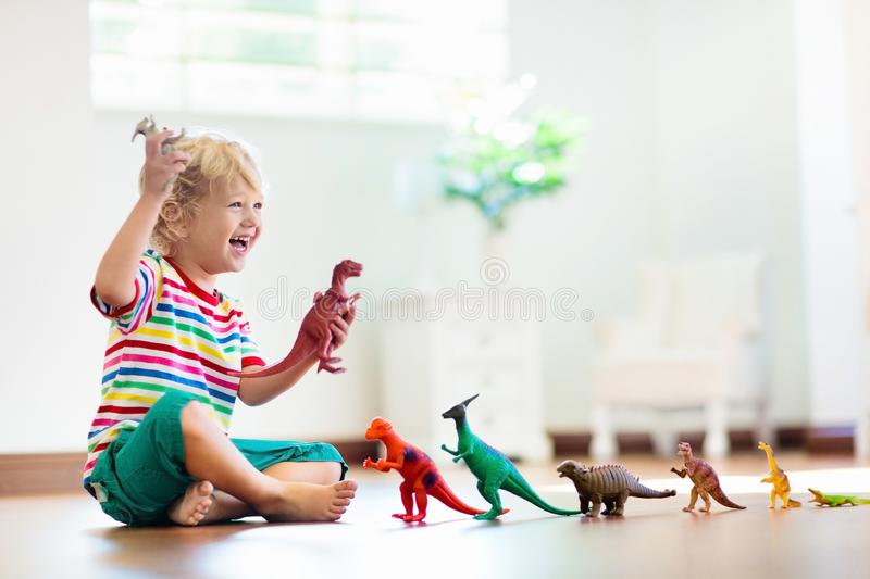 Child playing with toy dinosaurs. Kids toys royalty free stock images