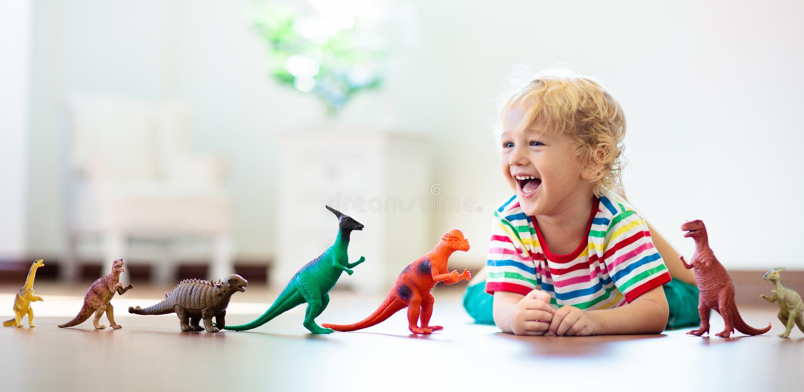 Child playing with toy dinosaurs. Kids toys royalty free stock photo