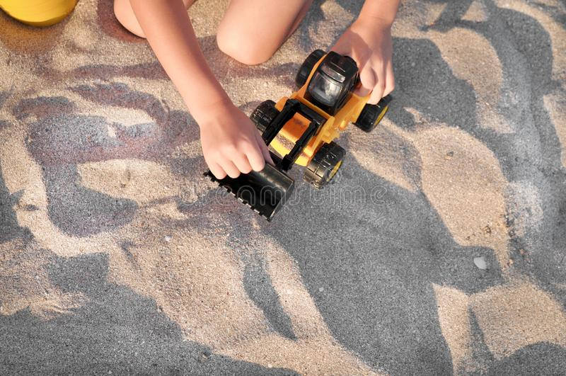 Child playing with a toy tractor on the beach. royalty free stock photos
