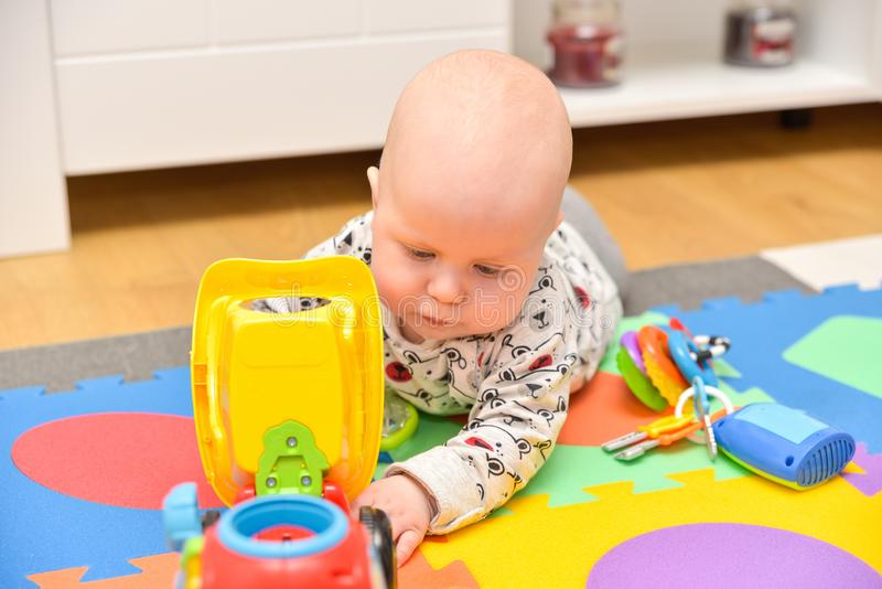 Child Playing Toys. Children Development Concept. Baby Kid. Adorable toddler boy playing with toys at home or daycare place royalty free stock photo