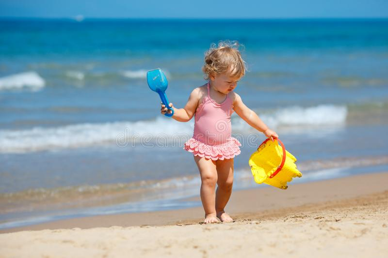 Child playing on tropical beach. Little girl digging sand at sea shore. Kids play with sand toys. Travel with young children. Child playing on tropical beach stock images