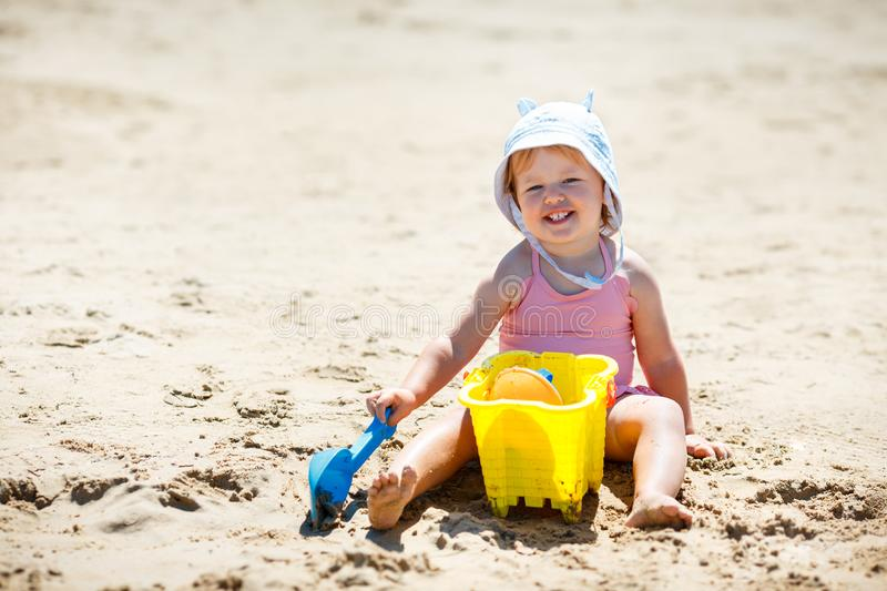 Child playing on tropical beach. Little girl digging sand at sea shore. Kids play with sand toys. Travel with young children stock photography