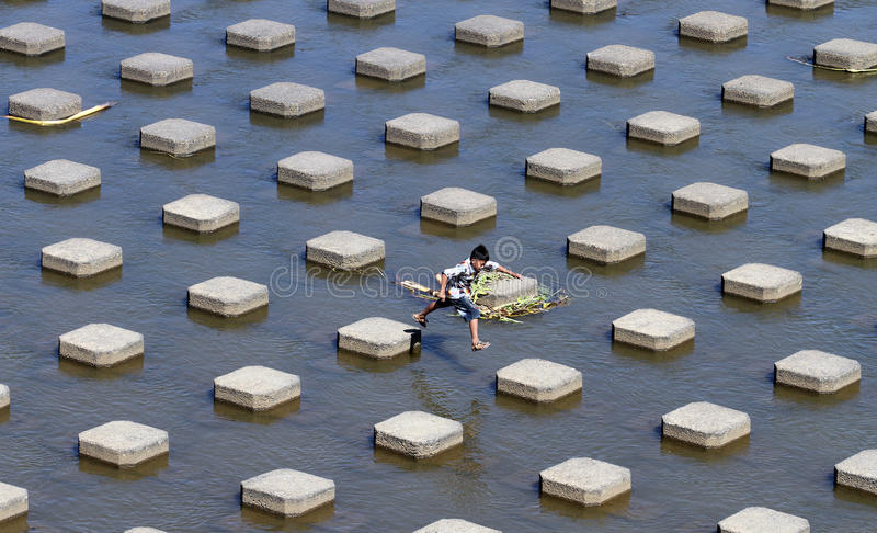 A child playing water in the Dam water Colo Nguter Sukoharjo Ce. Ntra Java Indonesia ( 29/6 ) . Dry season water dam of the reservoir elevation began to shrink stock image