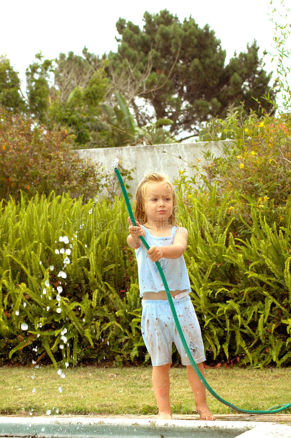 Child playing with water pipe. A cute little naughty caucasian girl child playing with a water pipe and having great fun in the garden outdoors royalty free stock image