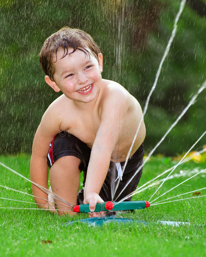 Child playing in water sprinkler stock image