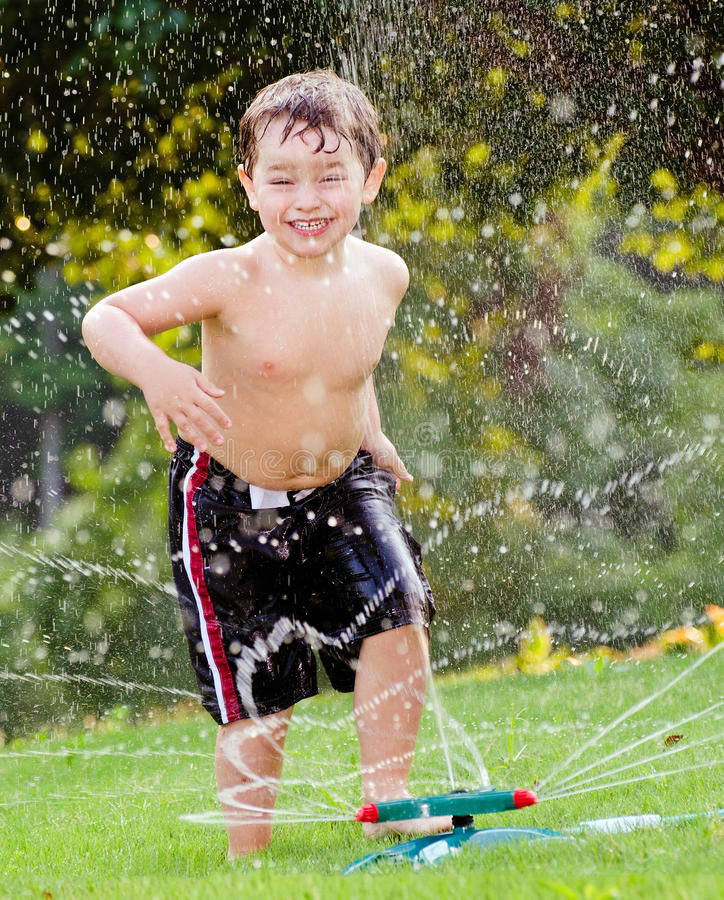 Child playing in water sprinkler stock images