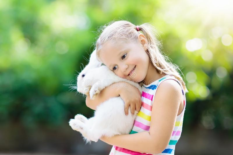 Child with rabbit. Easter bunny. Kids and pets. stock image