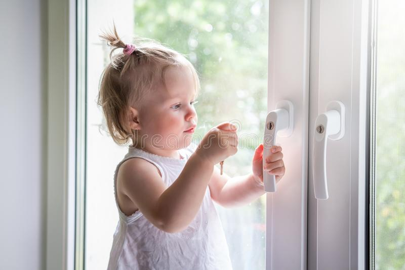 Child playing on window sill stock photos
