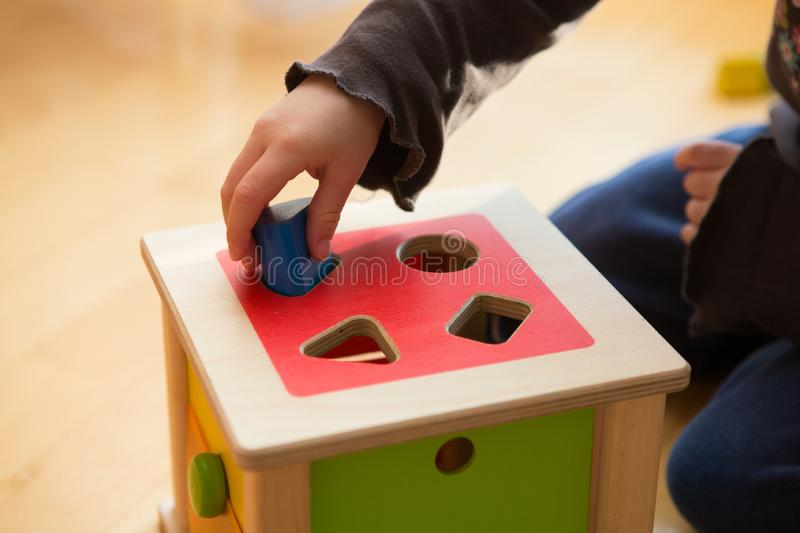 Child playing with wooden bricks in diffrent shapes and colors trying to put them into the proper hole. A child playing with wooden bricks in diffrent shapes and stock images