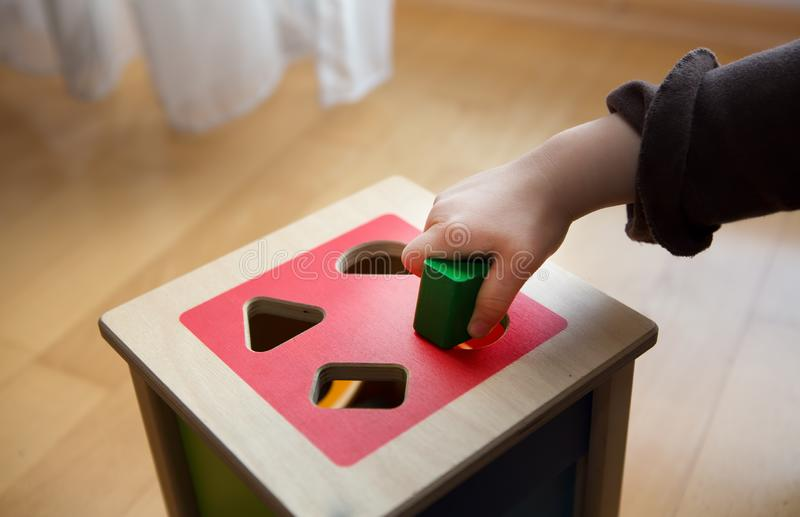 Child playing with wooden bricks in diffrent shapes and colors trying to put them into the proper hole. A child playing with wooden bricks in diffrent shapes and royalty free stock photography