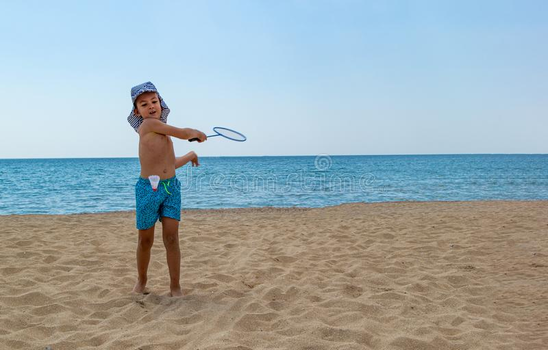 The child plays with a badminton racket and a shuttlecock on the beach royalty free stock images