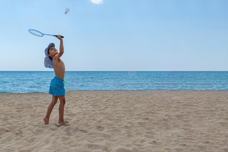 The child plays with a badminton racket and a shuttlecock on the beach. royalty free stock image