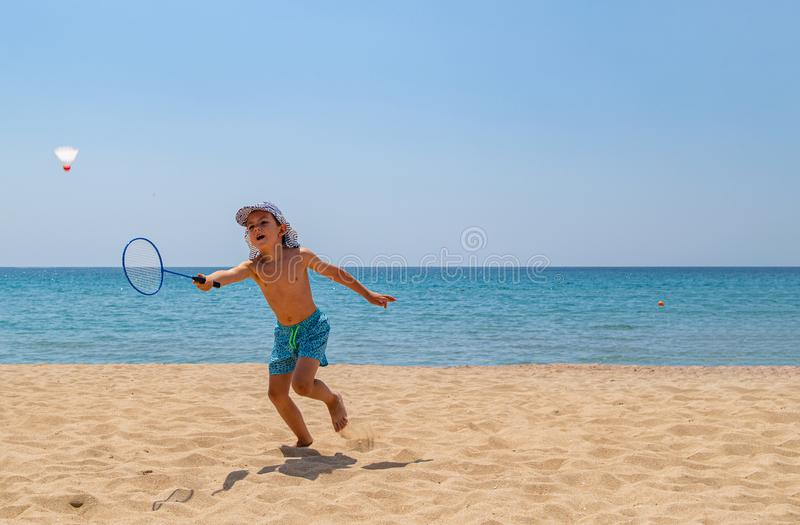 The child plays with a badminton racket and a shuttlecock on the beach royalty free stock image