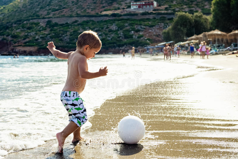 Child plays with a ball on the beach. stock photo