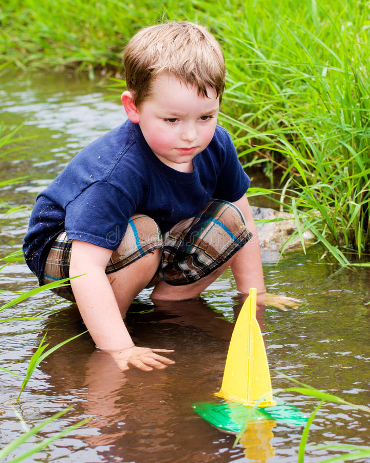 Child plays with boat in creek stock photography