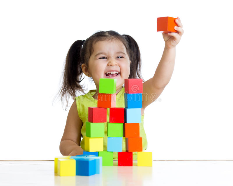 Child plays with building blocks and shows red royalty free stock photo