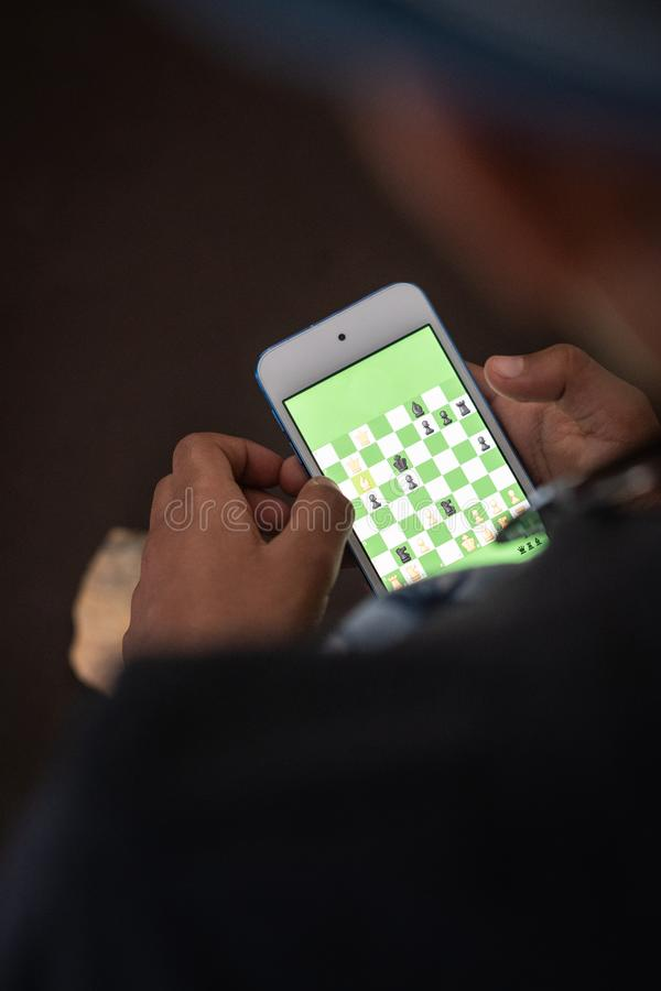A child paying chess on smartphone. stock photography