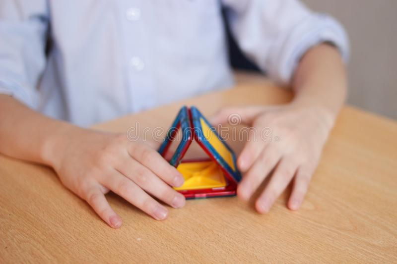 The child plays in the color designer on the table, builds a house, the concept of a family, the concept of building a new housing stock images