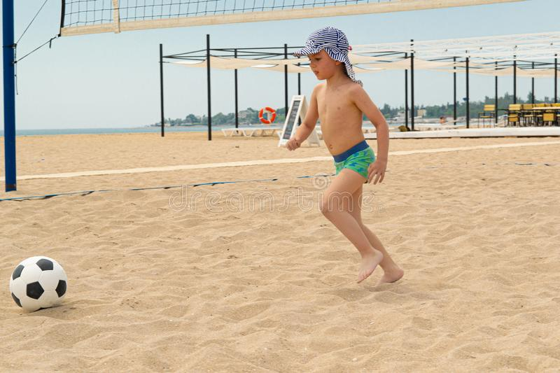 The child plays football on the beach. royalty free stock photography