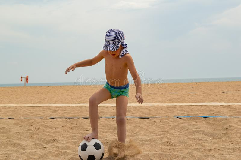 The child plays football on the beach. royalty free stock images