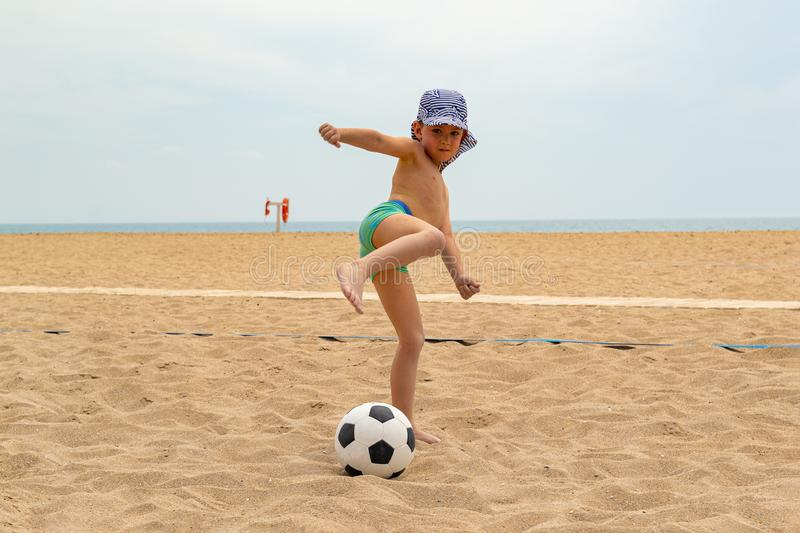 The child plays football on the beach. stock image