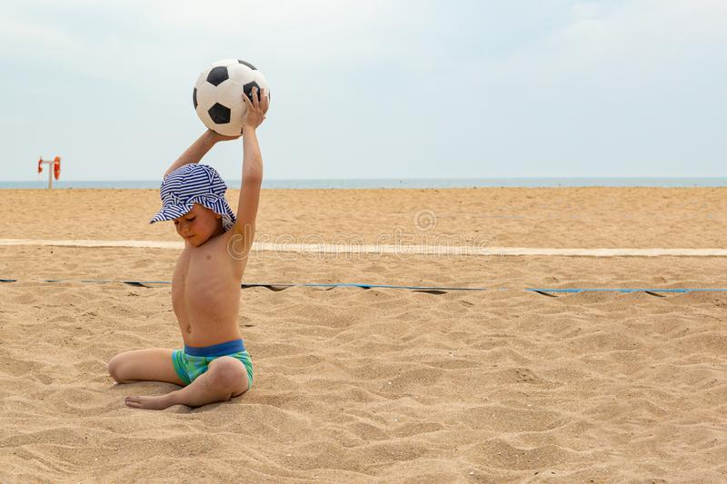 The child plays football on the beach. royalty free stock image