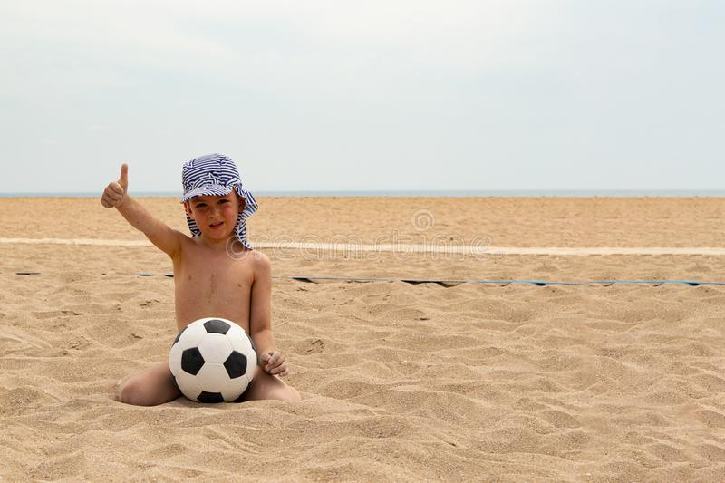 The child plays football on the beach. stock photo
