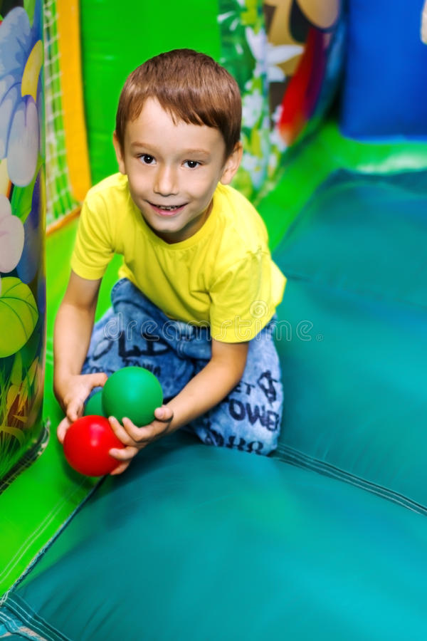 The child plays in an inflatable trampoline. stock photography