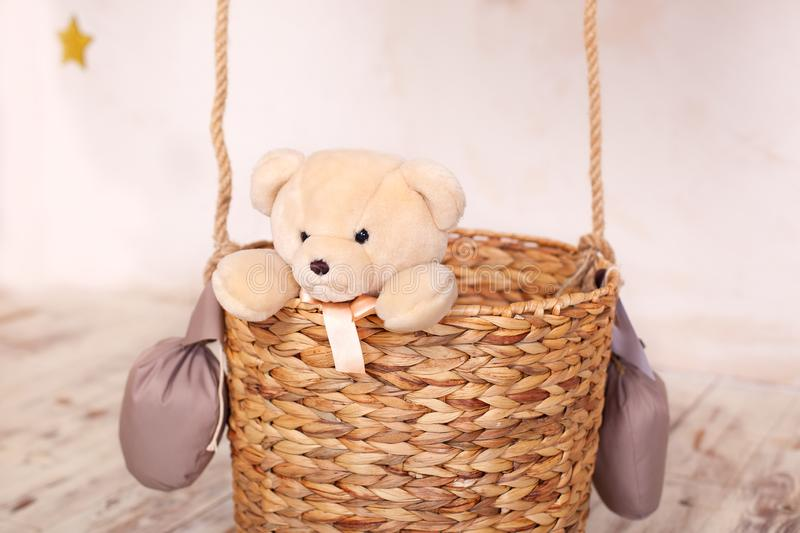 A child plays with a plush bear. Kids toys. Teddy sitting in the balloon basket, aerostat. Retro teddy bear. Toy teddy bear alone. In a basket. Sitting toy bear stock images