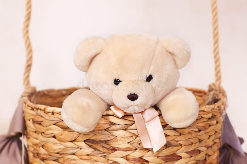 A child plays with a plush bear. Kids toys. Teddy sitting in the balloon basket, aerostat. Retro teddy bear. Toy teddy bear alone. In a basket. Sitting toy bear stock photo