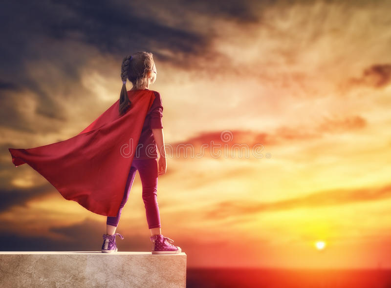 Child plays superhero. Little child plays superhero. Kid on the background of sunset sky. Girl power concept stock photography