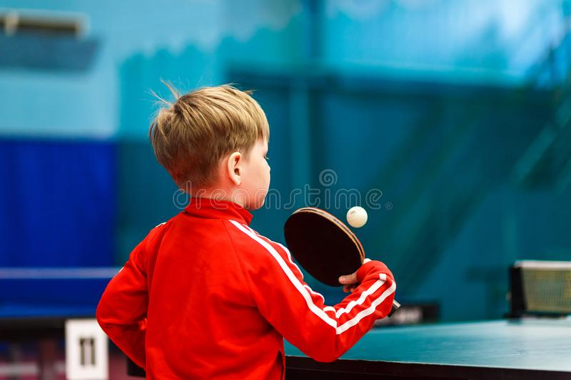 A child plays table tennis in the gym stock photo