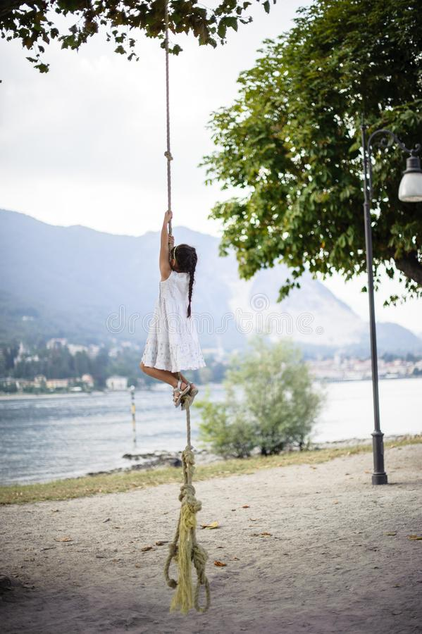 Little girl climbs on a big rope in the outdoor stock photo