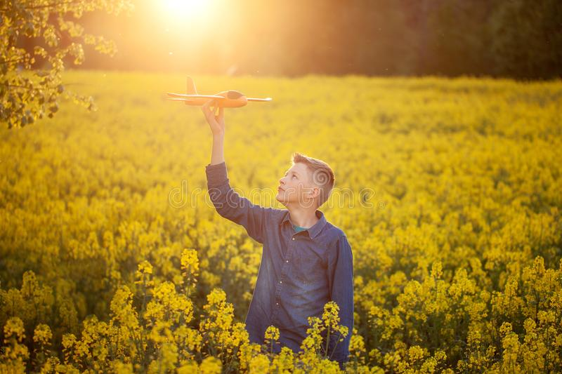 Child plays with a toy airplane in the sunset and dreams of journey in summer day stock photography