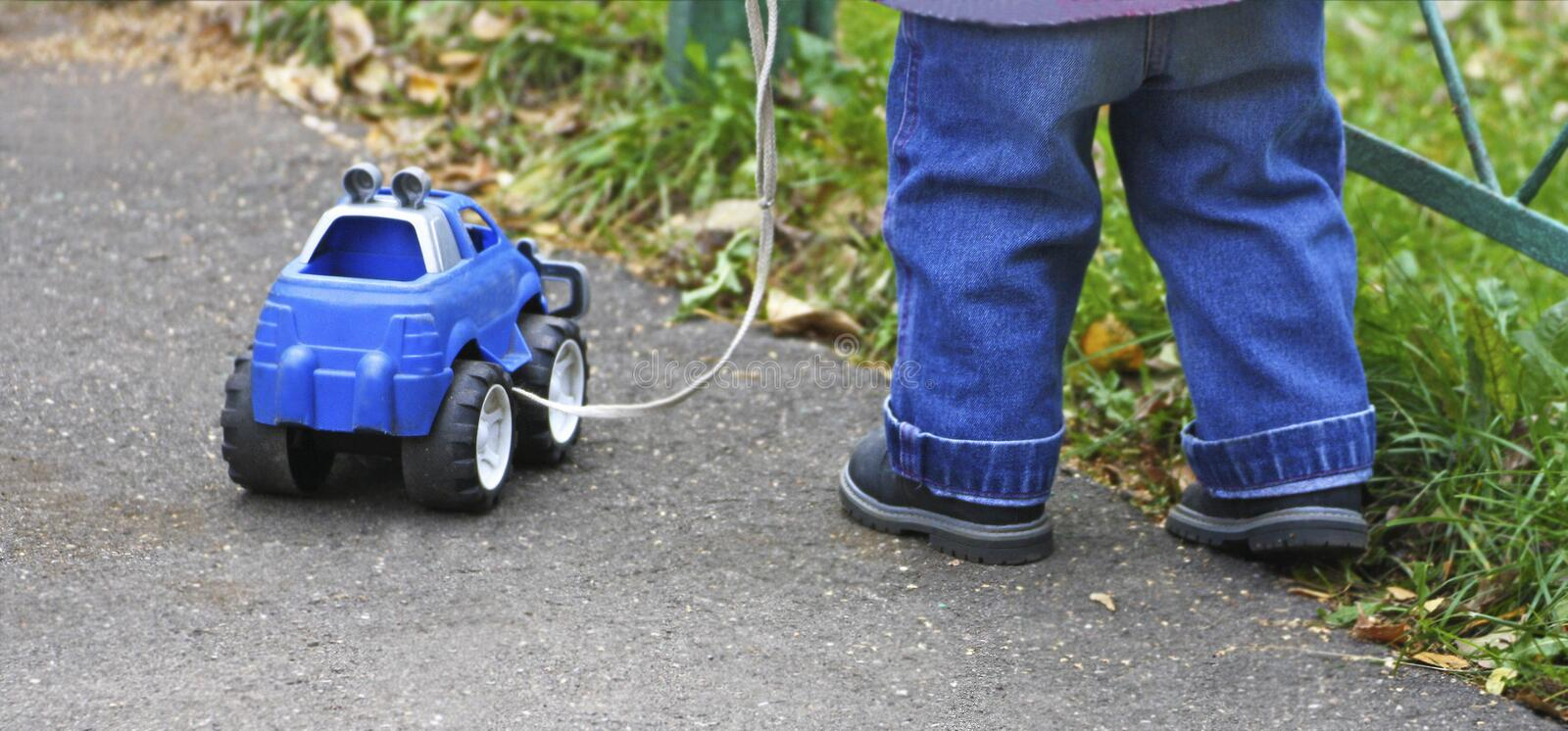 A child plays with a toy car and pulls it by a rope royalty free stock photo