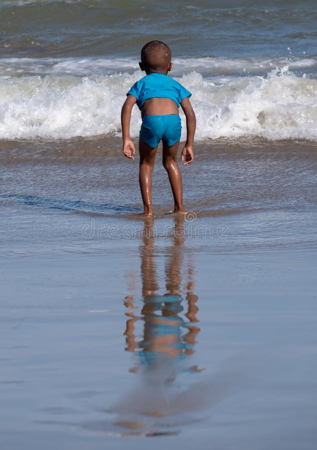 Child plays in the waves at Second Beach, Port St Johns on the wild coast in Transkei, South Africa. stock image