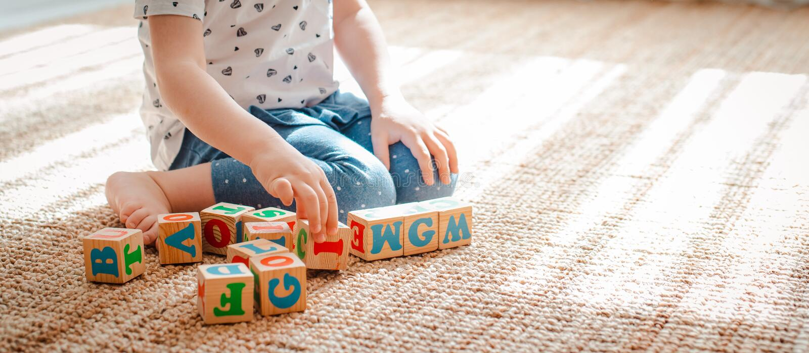 child plays with wooden blocks with letters on the floor in the room a little girl is building a tower at home or in the royalty free stock photos