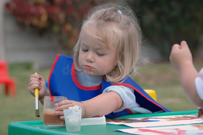 Child at playschool. A beautiful little caucasian girl child holding a paintbrush in her white hand painting a picture with water colors while sitting at a table stock photos