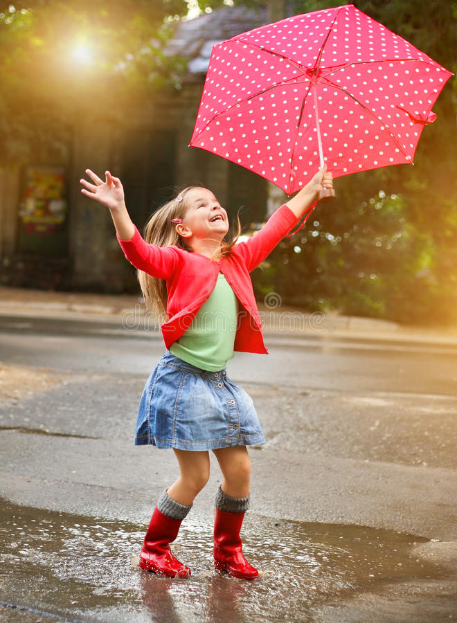 Child with polka dots umbrella wearing red rain boots royalty free stock photography