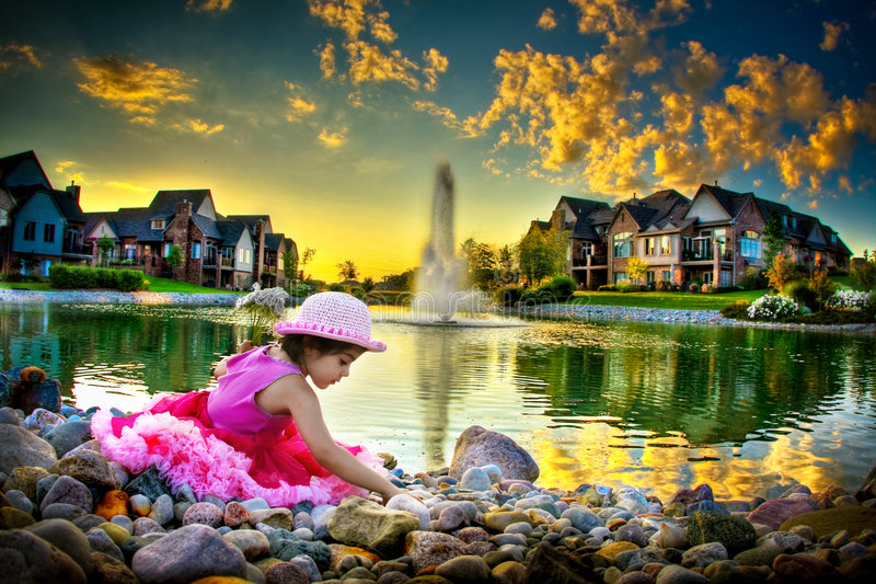 Child by the pond. LIttle girl sitting by the pond with gorgeous sunset colors all around royalty free stock photo