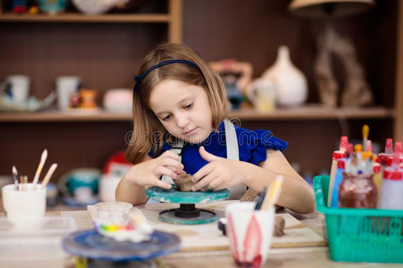 Child at pottery wheel. Kids arts and crafts class royalty free stock photo