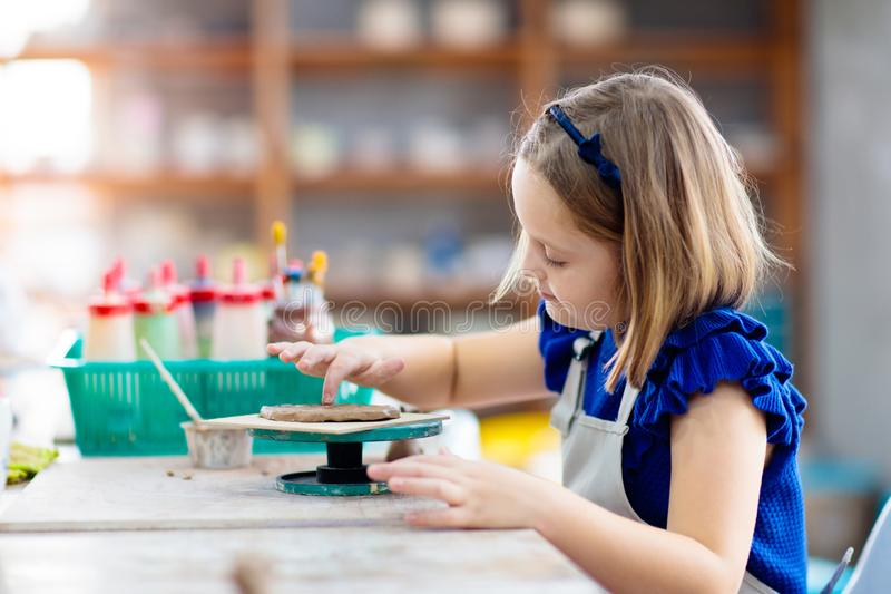Child at pottery wheel. Kids arts and crafts class royalty free stock image