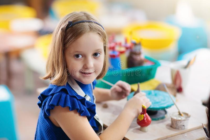 Child at pottery wheel. Kids arts and crafts class stock images