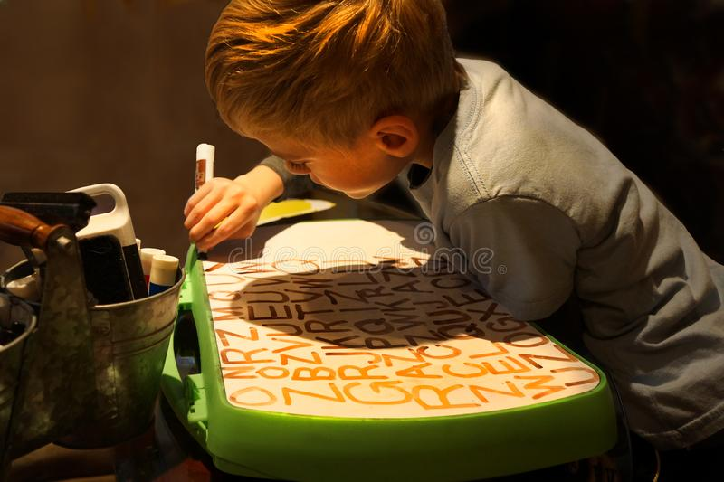 Child Practicing Writing Letters. Young boy practicing his letters on white board. Age six years. Cute little kid boy at home doing homework, writing with royalty free stock photography