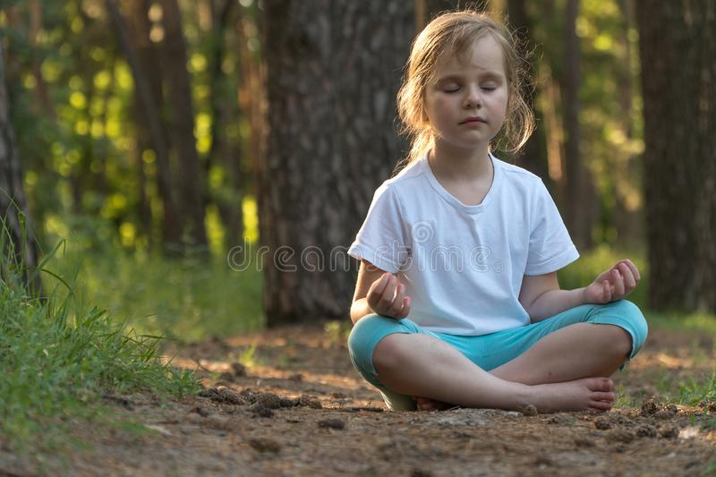The child is practicing yoga in the forest royalty free stock photo