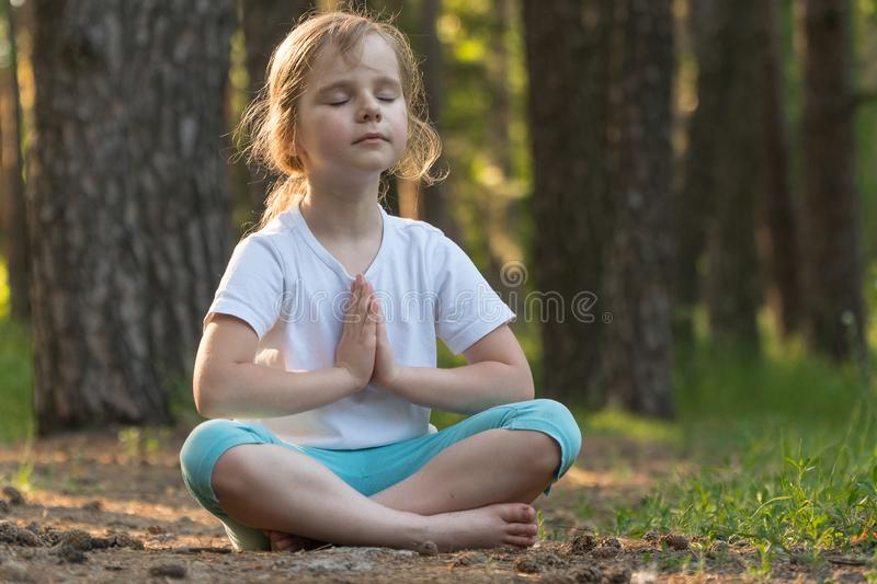 The child is practicing yoga in the forest stock photography