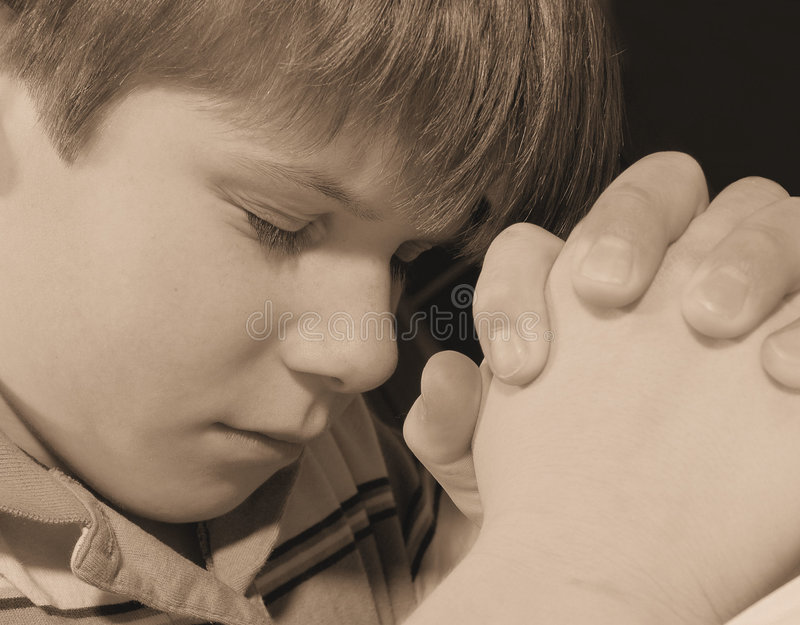 Child Praying. Young boy of Christian faith is praying. Done in sepia stock photography