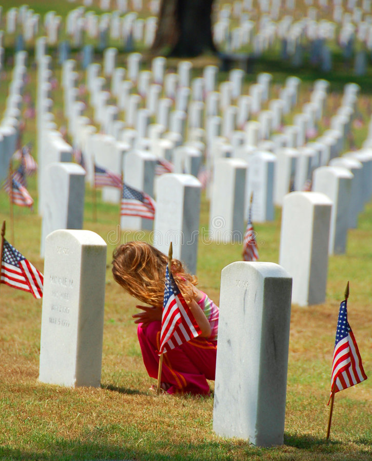 Child Praying in Cemetery. Child bent over in thoughtful prayer in military cemetery stock photography